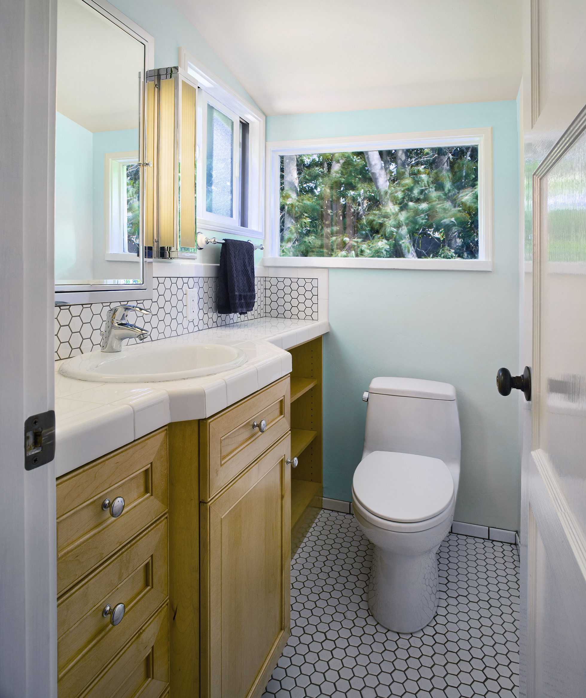 Light blue bathroom with white sink, toilet, and tile