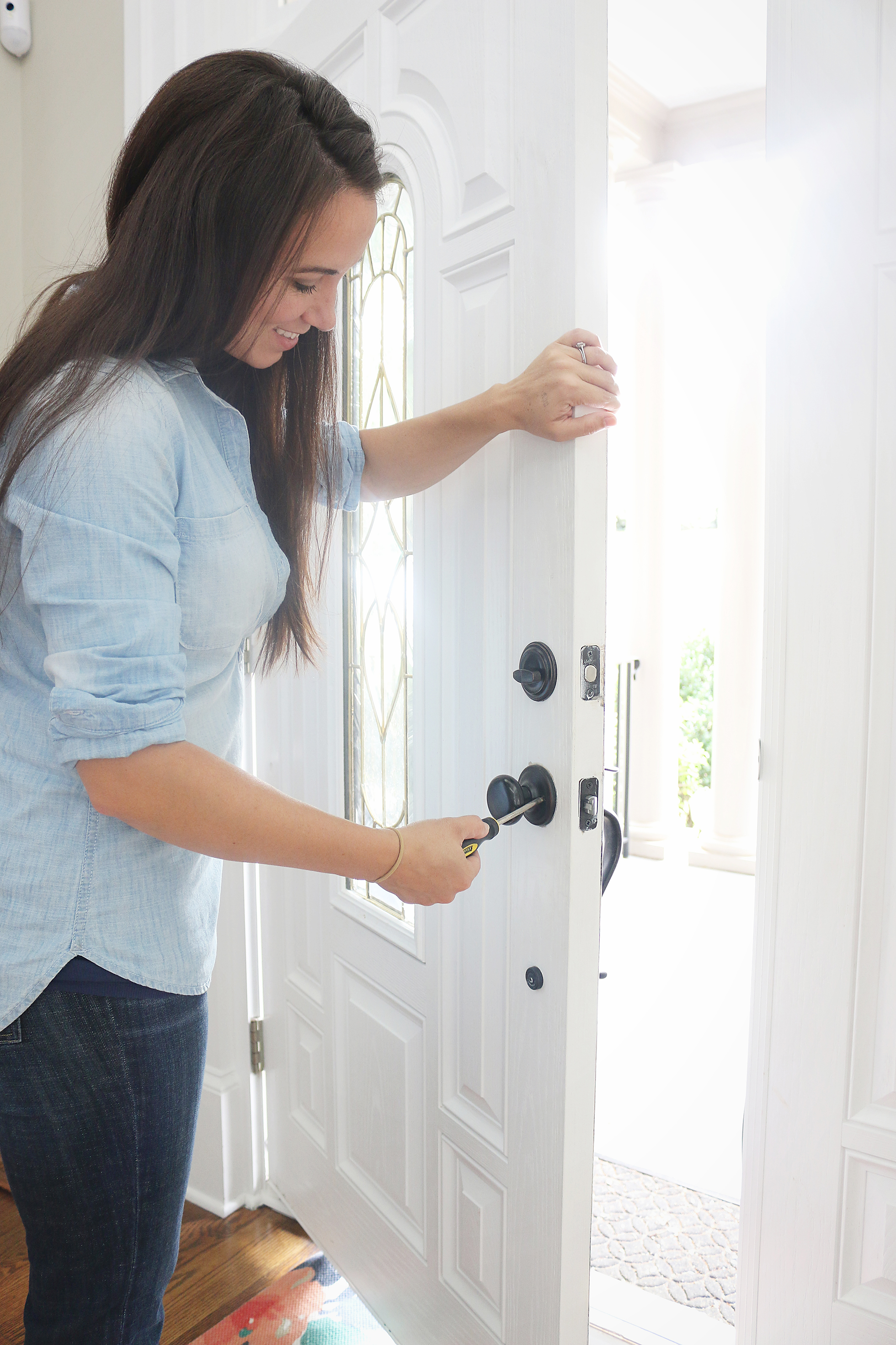 Woman securing a front door lock