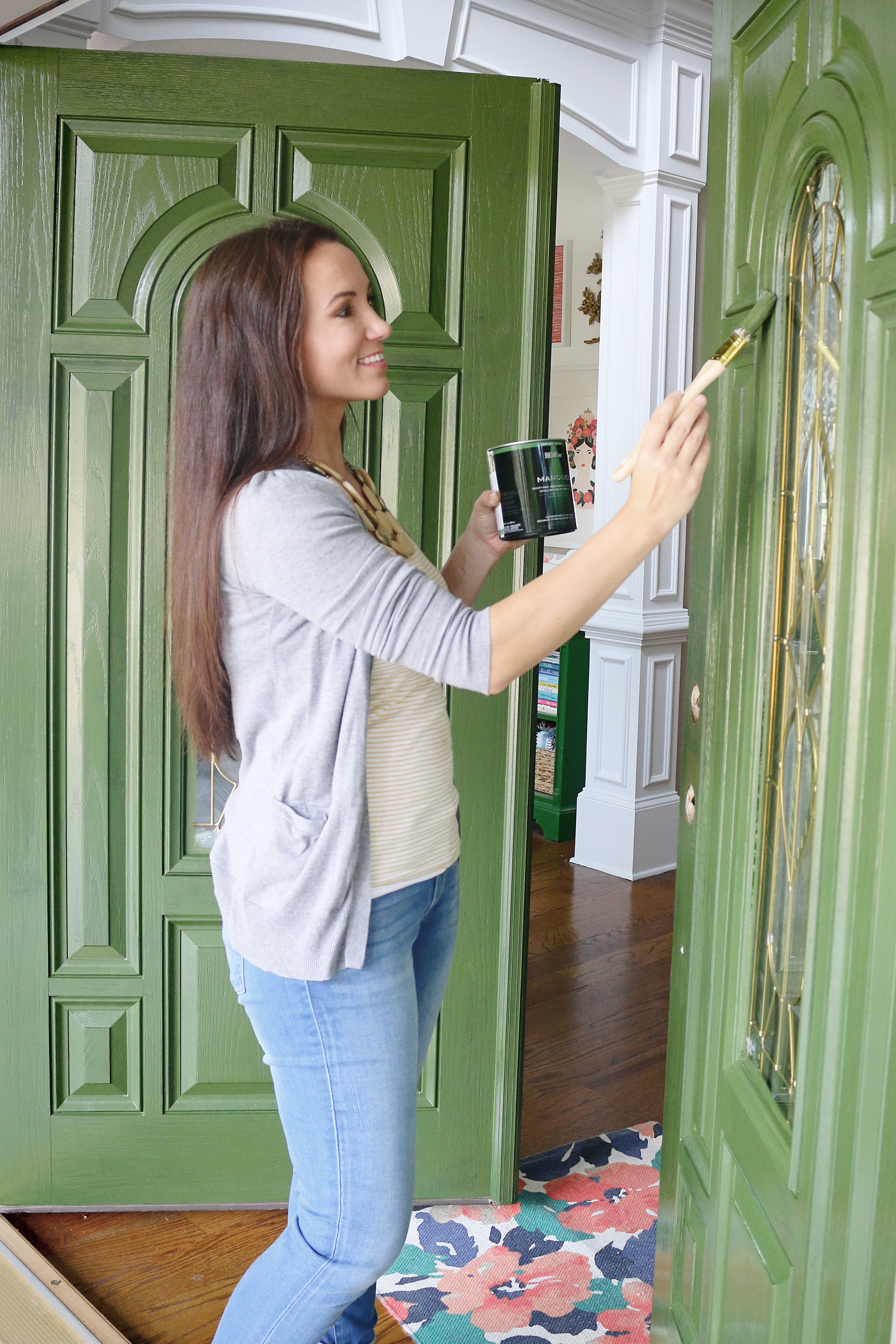 Woman painting her front door green