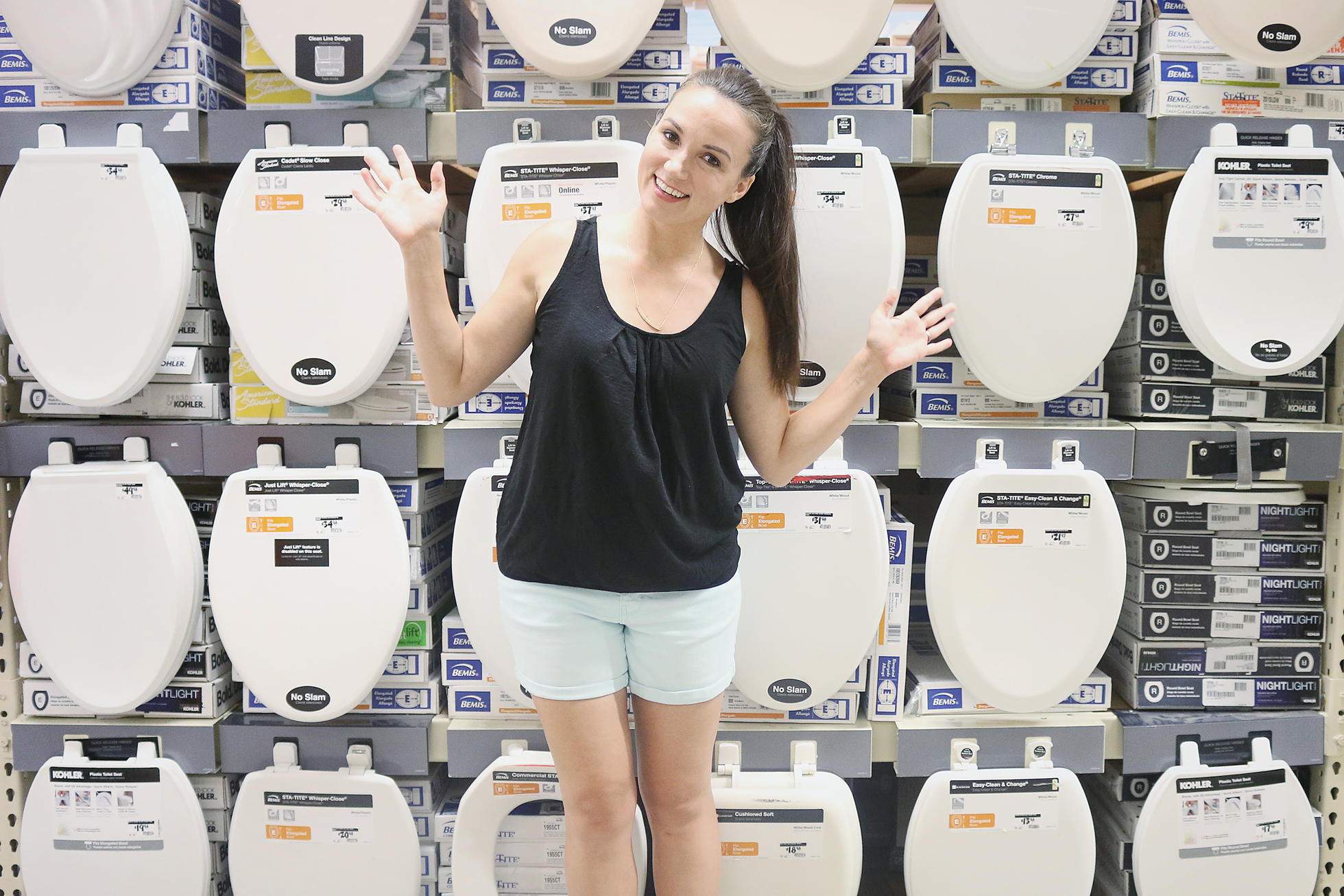 Woman standing in front of toilet seats on a wall