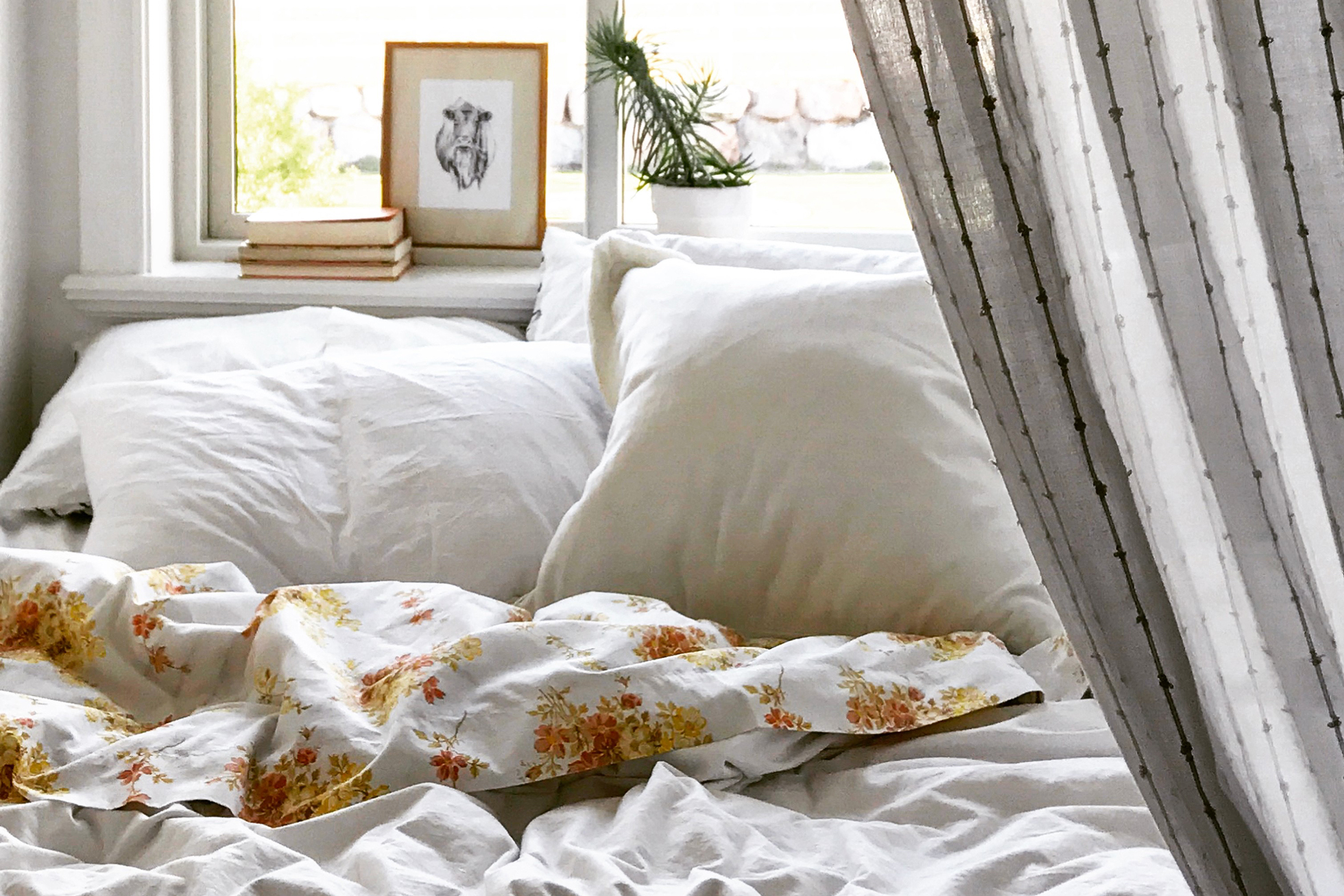 A bed with white sheets and a white bedspread by window