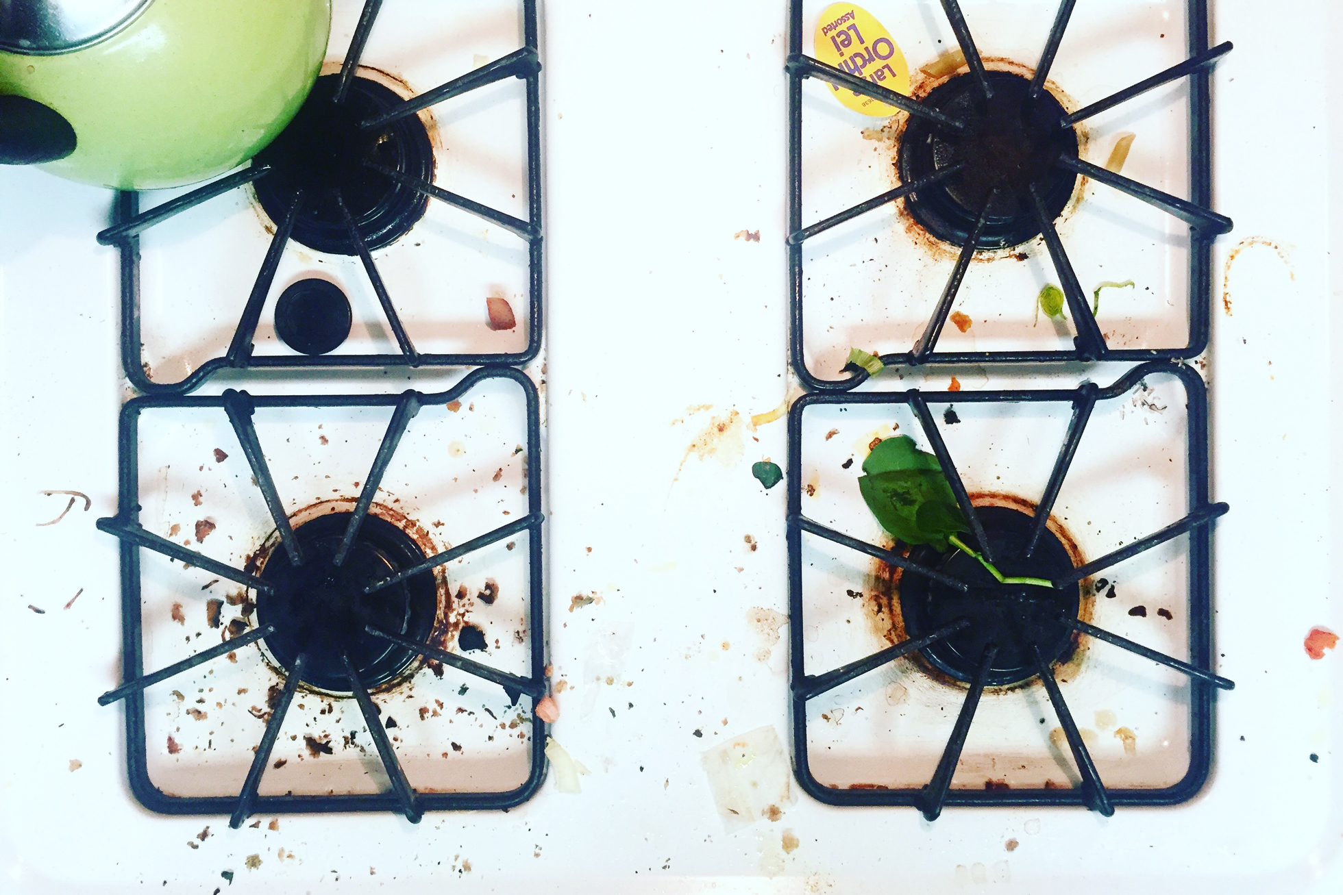 A gas stovetop with food crumbs, green teapot