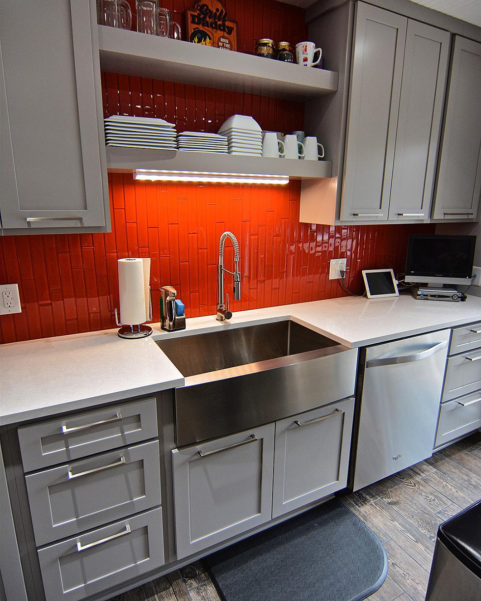 Orange tile backsplash in white kitchen with stainless sink