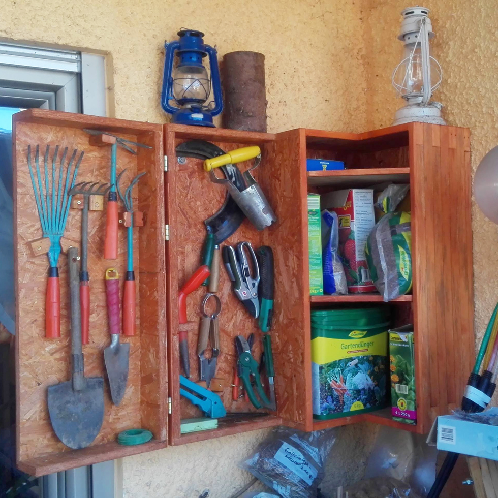 Wood cupboard with tools attached to stucco outside wall