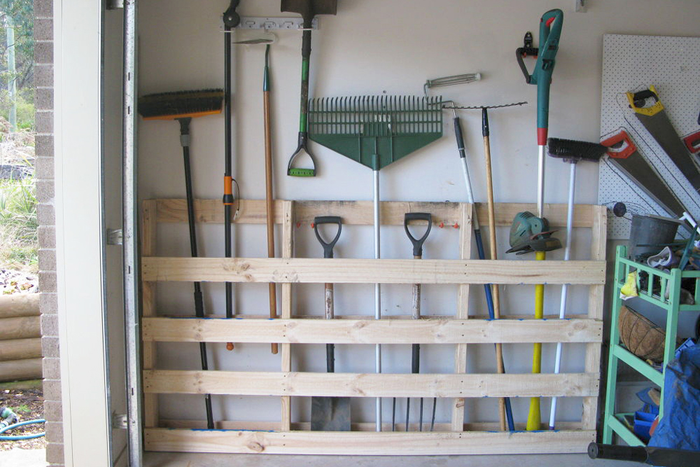 A pallet against a garage wall with outdoor tools