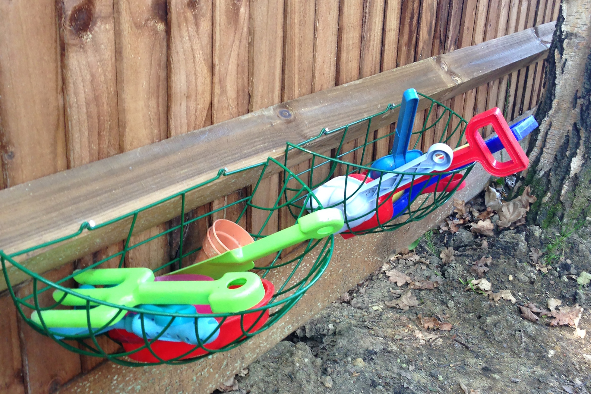 Green wire baskets with plastic kids tools on a fence