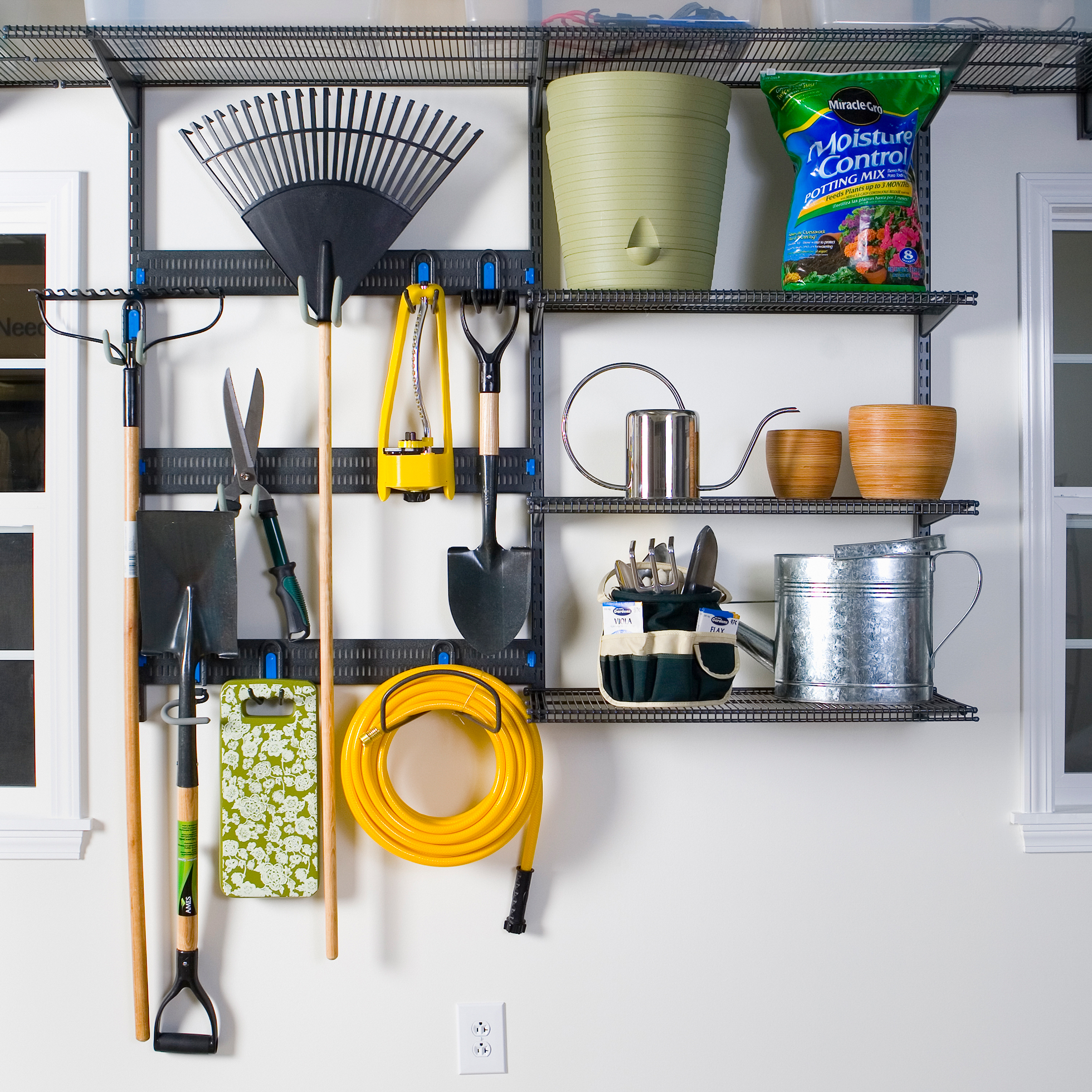 Black vertical shelving with garage tools inside a garage