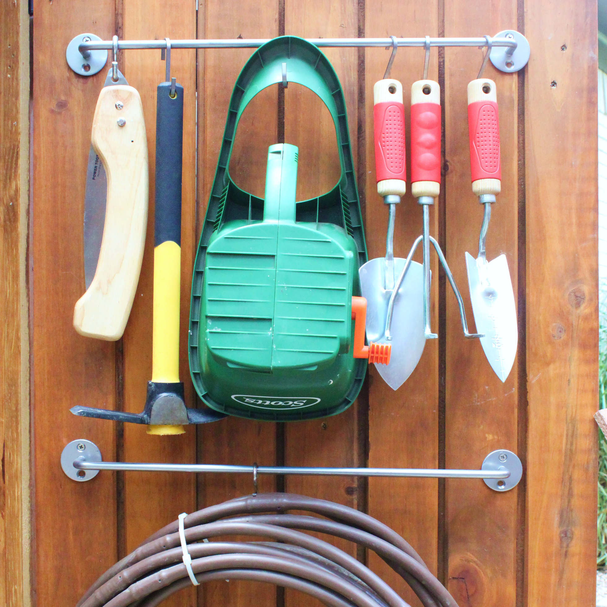 Outdoor tools hanging from s hooks on a wood door