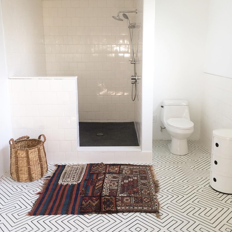 A white tile bathroom with walk-in shower