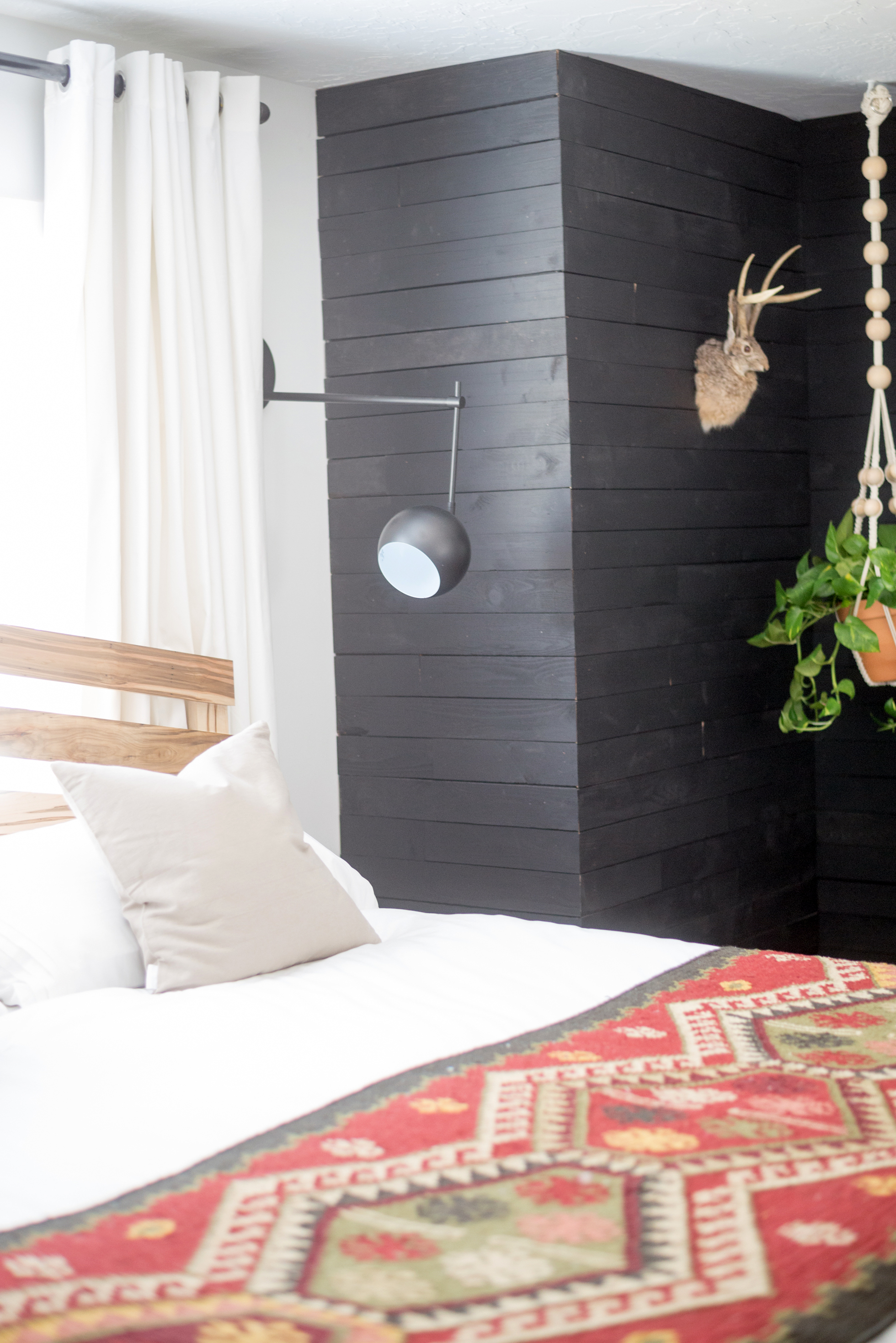 Black accent wall in a bedroom