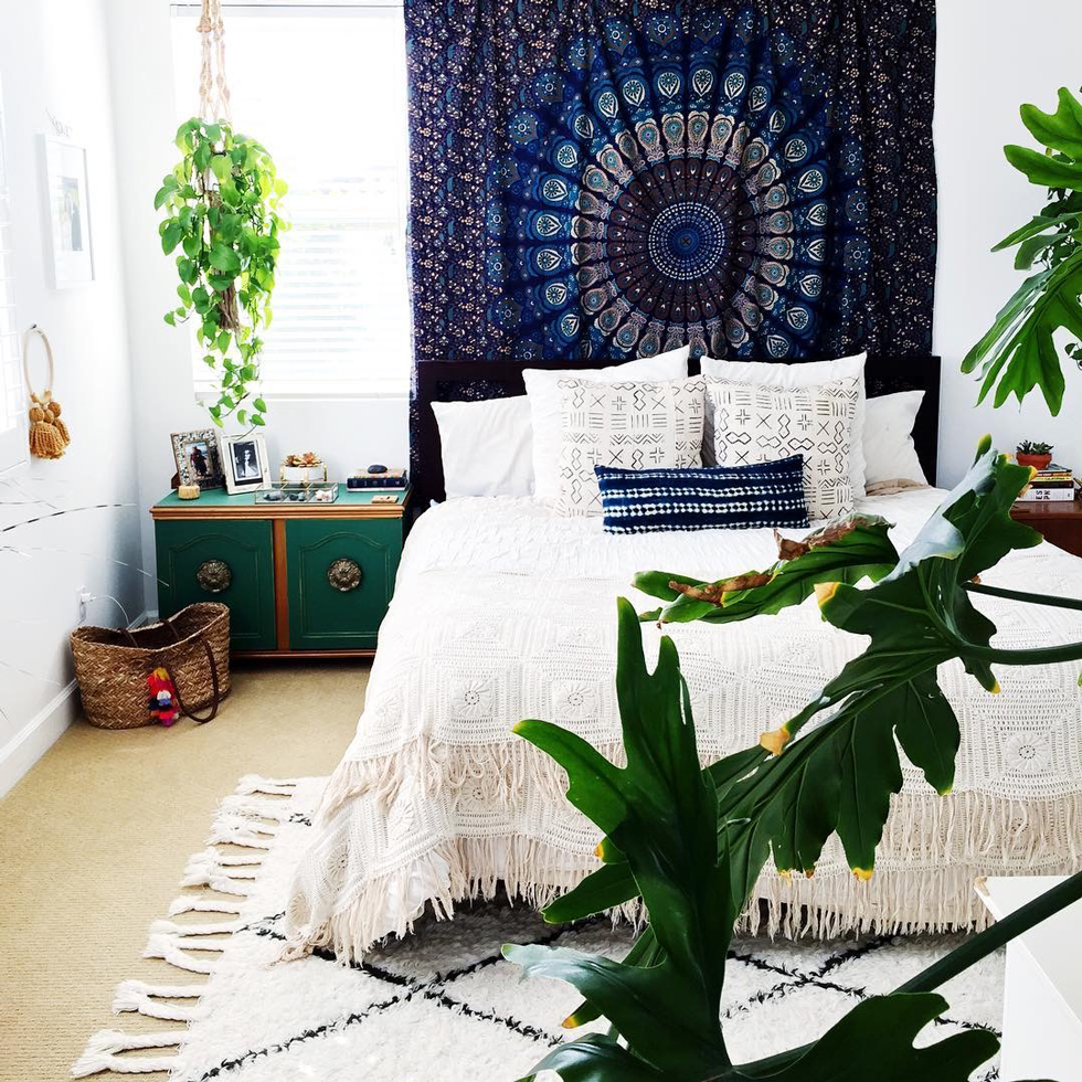 A bright bedroom with a blue tapestry and lots of plants