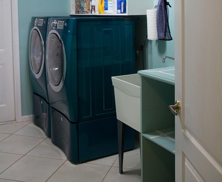 A teal washer and dryer combo in a light-blue laundry room