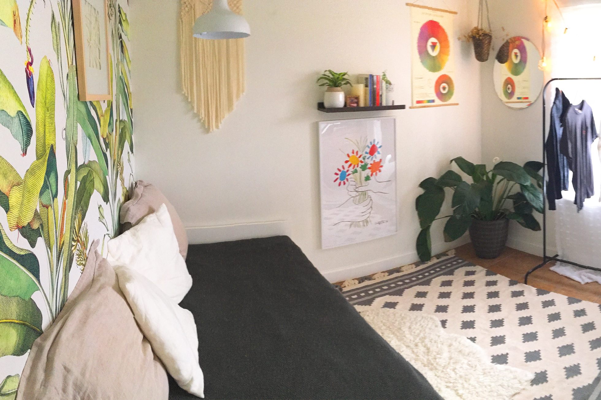Bright room with tropical wallpaper and a black daybed