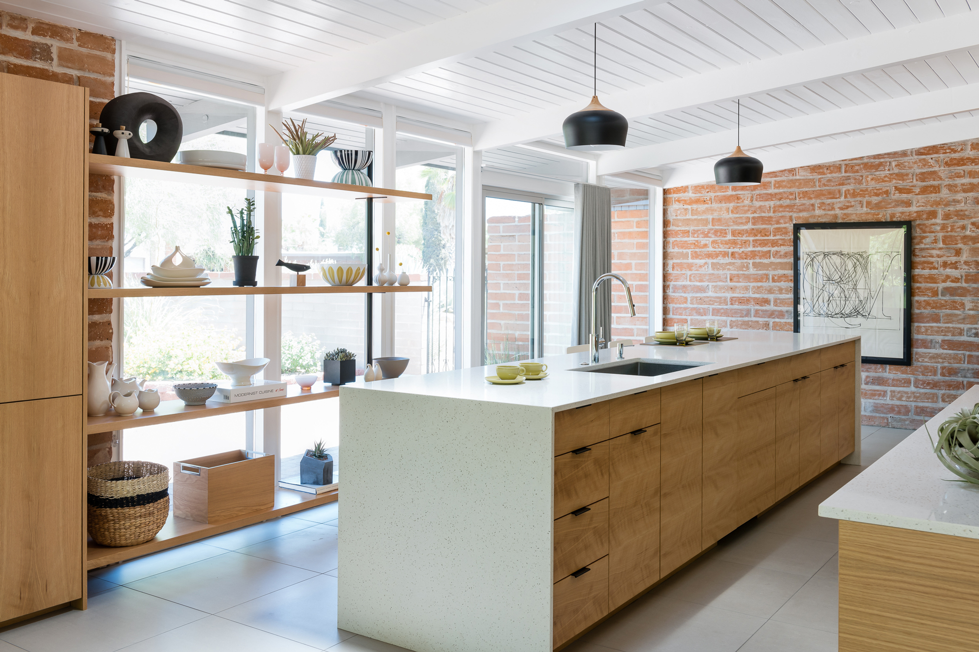 A bright kitchen with open shelving and wall of windows