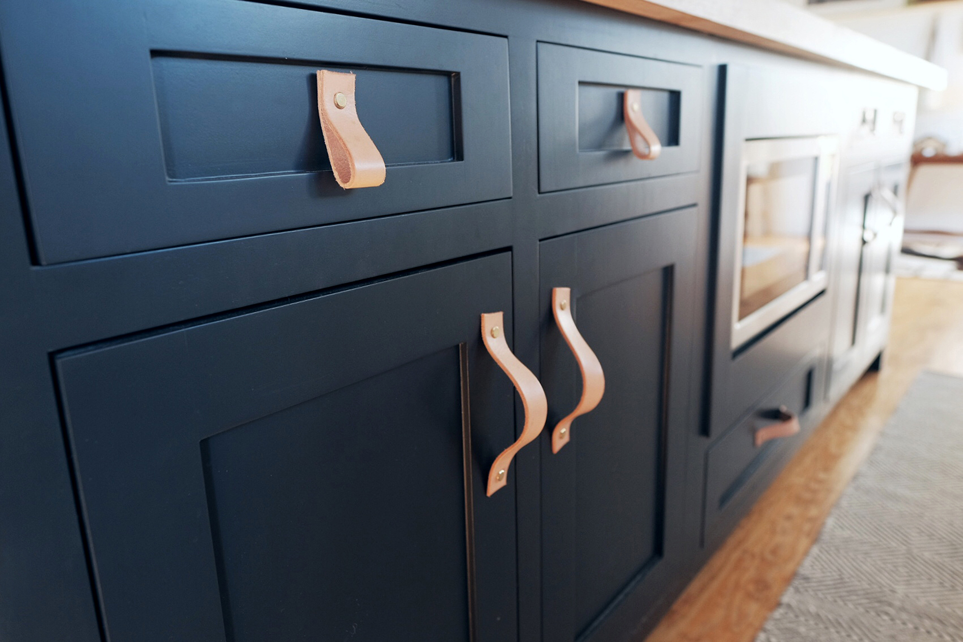 Navy blue cabinets with light brown leather drawer pulls