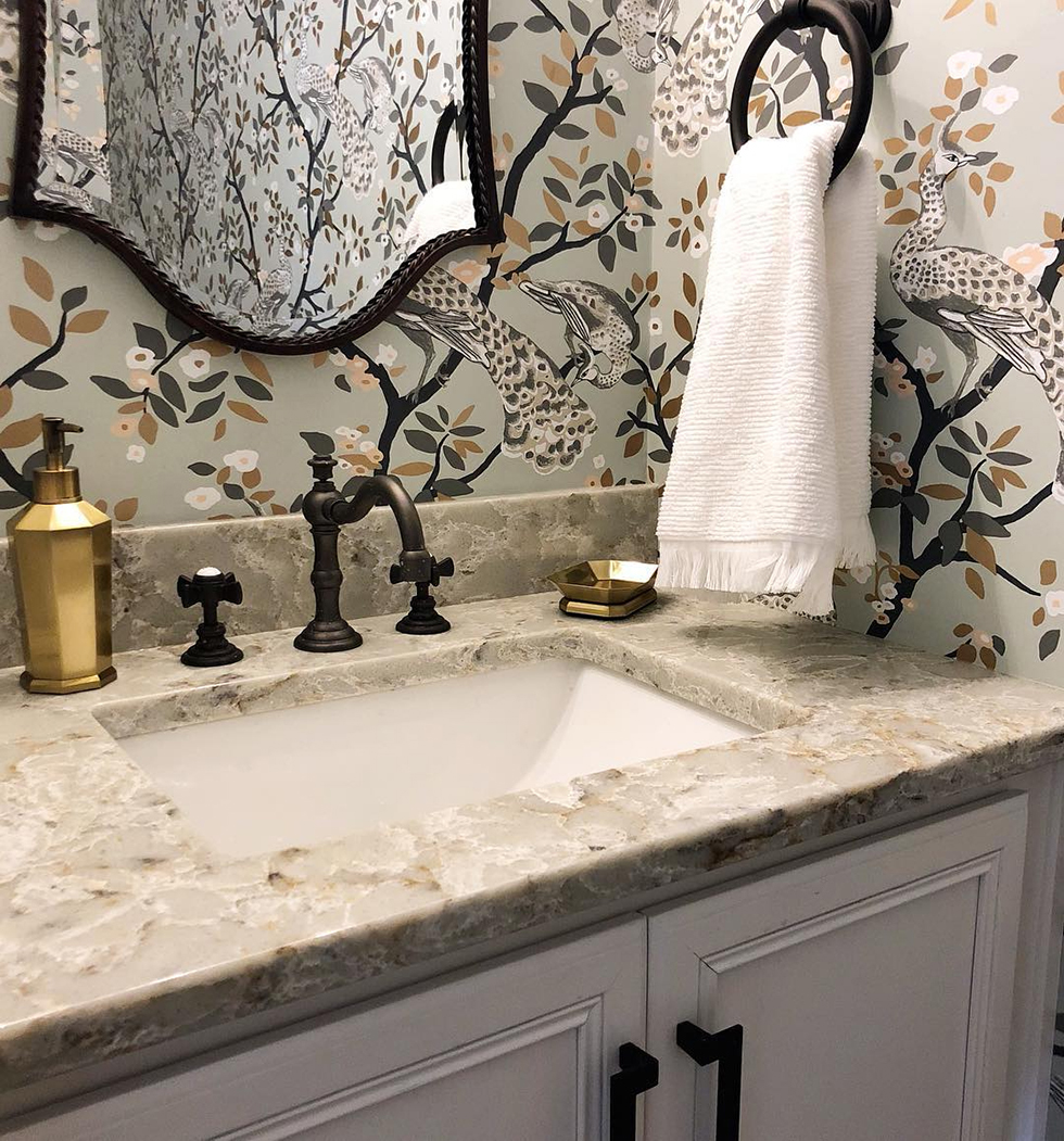 Marble sink with dark brass facet and gray wallpaper