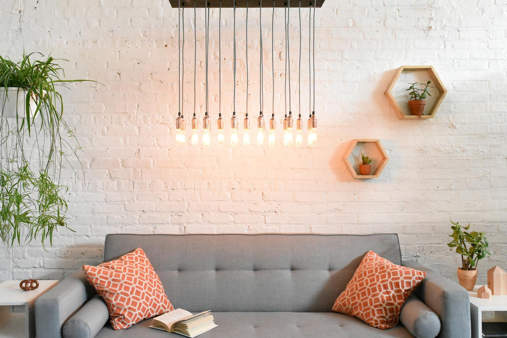 Wood chandelier with Edison bulbs over couch in living room